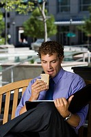 Businessman sitting on a bench,eating a sandwich