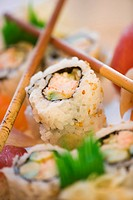 Close_up of sushi rolls with chopsticks