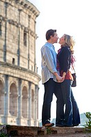 Couple kissing at the roman Colosseum Rome Italy