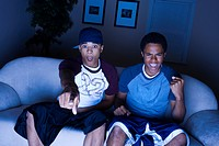 High angle view of a young man and a teenage boy sitting on a couch watching television