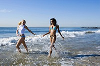 Two young women running in the water on the beach