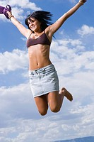 Low angle view of a young woman holding her top and jumping