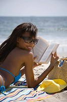 Rear view of a young woman reading on the beach