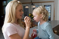 Side profile of a mother feeding her daughter with a spoon