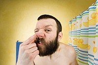 Man with beard in bathroom picking nose