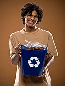 young man in a brown shirt holding a recycling bin.