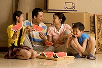 Family of four eating watermelon and smiling with cardboard boxes in background