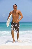 Man with surfboard on beach smiling