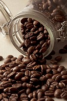 Detail of coffee beans spilling from a jar