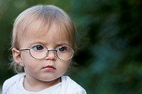 A young girl wearing glasses frowns in concentration while looking away