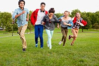 Teenagers running in a park