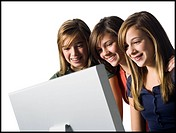 Three girls looking at computer monitor smiling