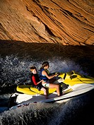 Two people on personal water craft with rock formations
