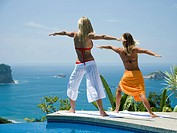 Two women performing yoga exercises by infinity pool