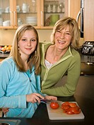 Portrait of a girl cutting tomatoes with her mother leaning against a kitchen counter
