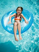 Young girl floating on life ring in swimming pool