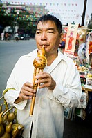 Man playing a Chinese woodwind instrument