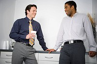 Close_up of two businessmen leaning against a drawer and looking at each other