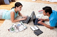Man and woman lying on carpet with laptops