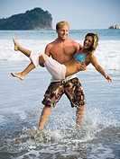 Man carrying girlfriend on beach