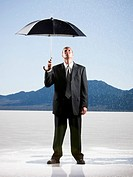 businessperson holding an umbrella in the desert