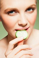 Woman biting piece of cucumber