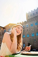 Young woman on cellphone at restaurant outdoors