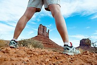 Low angle view a sandstone butte between a woman's legs in the Monument Valley, Arizona. USA