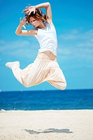 Teenage girl dancing hip_hop and jumping on beach, summer series