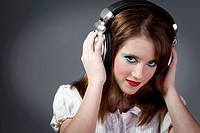 Young girl in headphones on a grey background