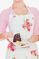 Woman in apron holding plate of tempting pastry