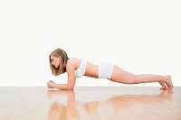 Side view of woman doing push_ups on hardwood floor