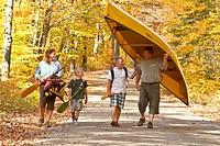 Family portaging canoe, Algonquin Park, Ontario, Canada.