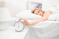Irritated woman in bed extending hand to alarm clock