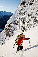 A male backcountry skier bootpacks up a steep and exposed coulior on Mt. Patterson, Icefields Parkway, Banff, AB