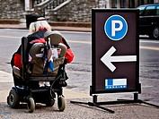 An elderly man in a motorized wheelchair rolls past a parking lot sign.