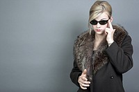 Young woman with sunglasses and a fur coat