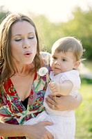 Young mother with her daugther, blowing a dandelion clock, Old Danube, Vienna, Austria