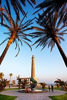 View through palm trees onto promenade and lighthouse, Maspalomas, Gran Canaria, Canary Islands, Spain, Europe