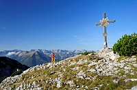 Woman walking towards cross at summit, Unnuetz, Unnutze, Rofan mountain range, Brandenberg Alps, Tyrol, Austria