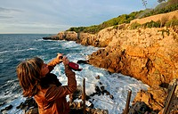 Woman taking a photo of the rocky coast, Le Chemin des Contrebandiers at Cap d'Antibes, Cote d'Azur, South France, Europe