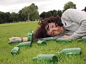 Woman lying over grass with bottles