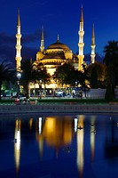 lights on Blue Mosque at dusk with reflections in fountain Istanbul Turkey