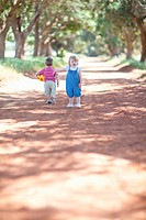 Toddlers playing on dirt road