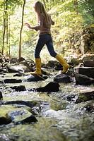 Woman walking on rocks in stream