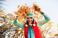 Portrait of smiling young woman throwing dry leaves in autumn forest