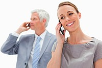Close_up of a smiling woman making a call with a white hair businessman in backg