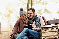 Couple using tablet computer in park