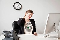Studio shot of young woman working in office and touching her neck