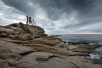 Couple standing on boulder by ocean